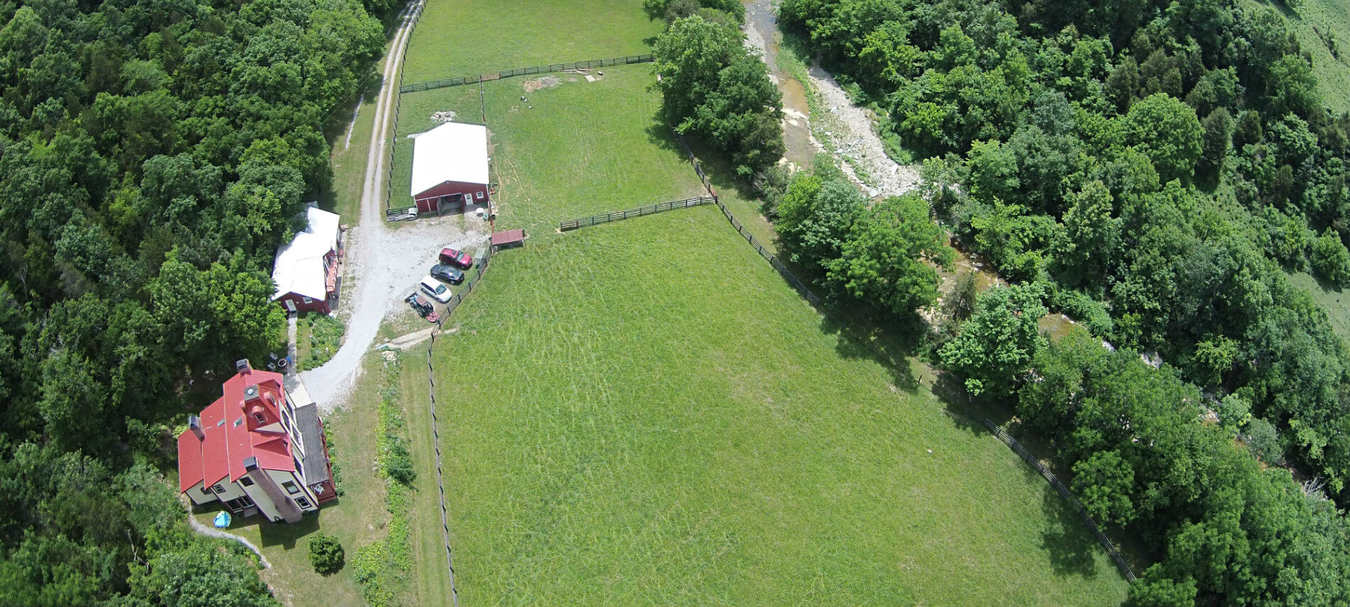 Arial view of the farm shows fenced green paddocks and the outline of the Otter Creek