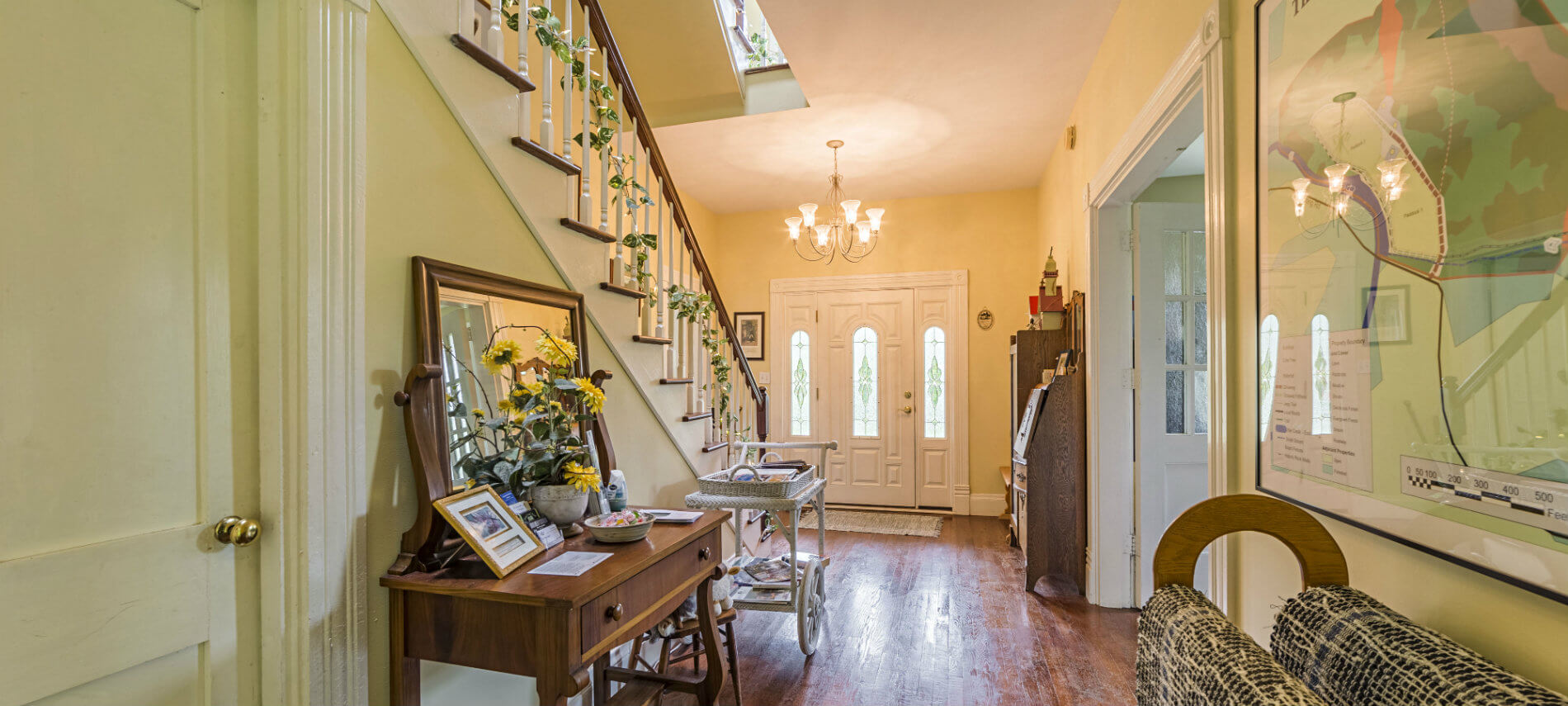 A bright entrance hallway displays blue rag rugs, chandelier and stairway to second floor