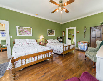 The sage green Meadow Room has two double beds and two comfortable chairs