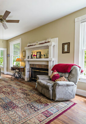 The Living Room has two chestnut sofas, several comfortable recliners, an oriental rug and a fireplace.