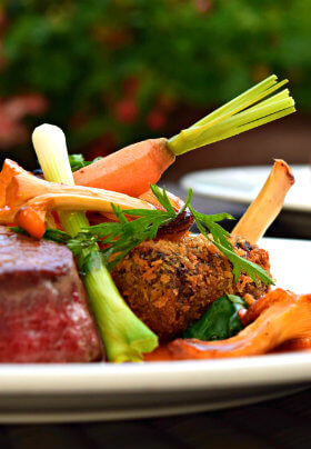 A delicious plate of grilled steak with fresh yellow carrots and seasonal vegetables.